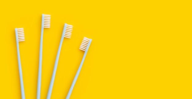 Escovas de dentes em fundo amarelo. vista do topo