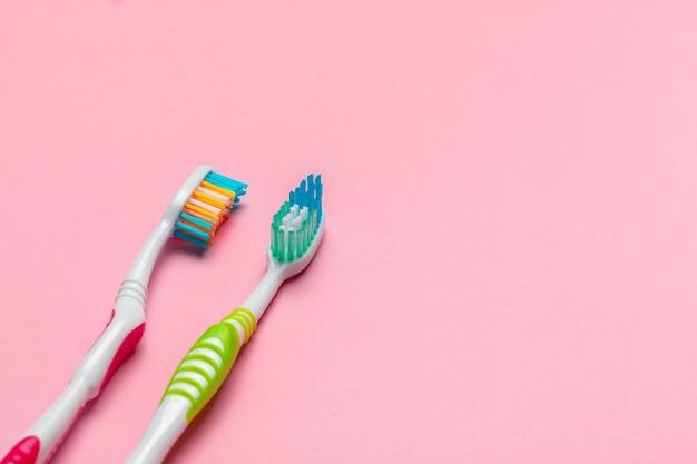 Escovas de dentes em fundo rosa