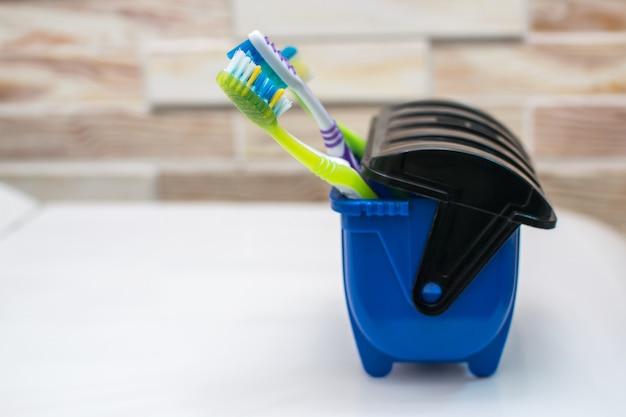 Escovas de dentes em uma lata de lixo azul, muitos germes então jogados fora