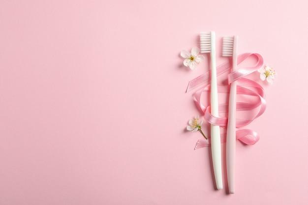 Escovas de dentes, fita e flores na superfície rosa