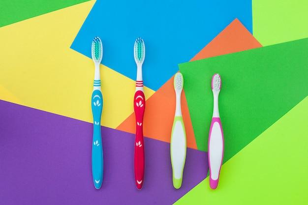 Escovas de dentes no fundo brilhante colorido. conceito de higiene familiar.