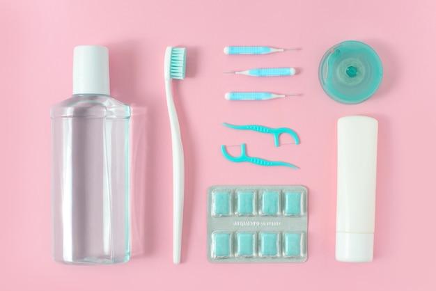 Escovas de dentes, pasta de dentes, enxágue e goma de mascar em fundo rosa