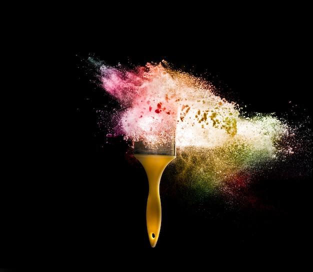 Escovas de pintura com explosão abstrata da cor do pó isolada no conceito preto da cor completa do fundo.
