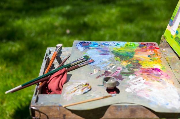 Escovas de pintura usadas em uma paleta colorida do pintor