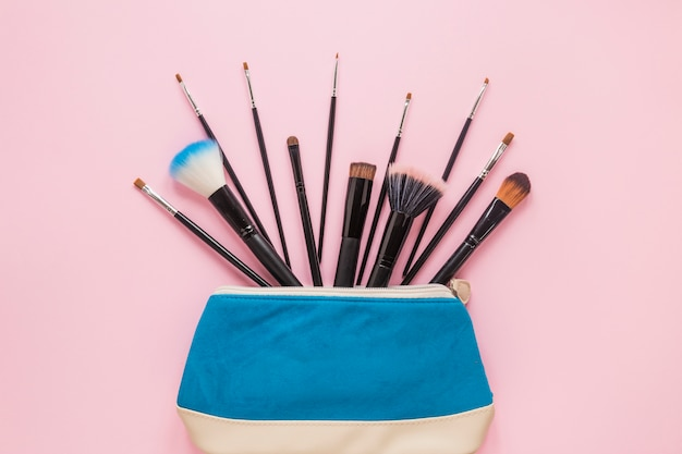 Escovas de pó diferentes em bolsa de beleza