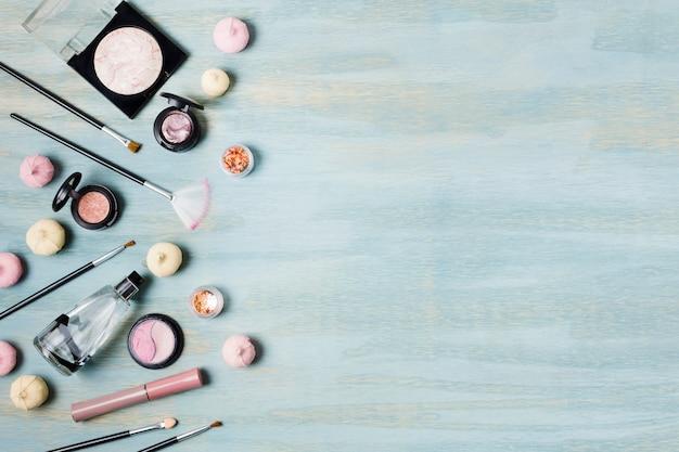 Escovas de sombra e cosméticos ao lado de doces