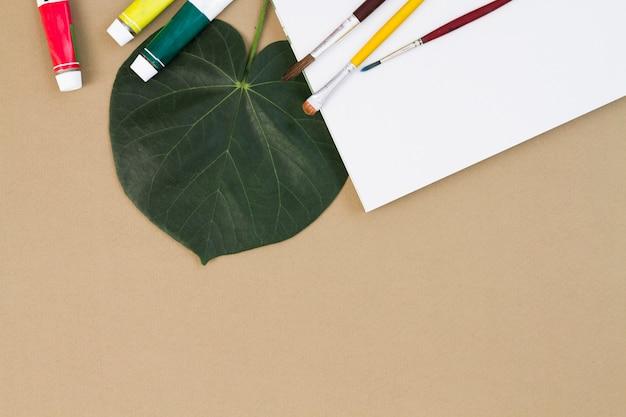 Escovas e tintas espalhadas na folha de papel