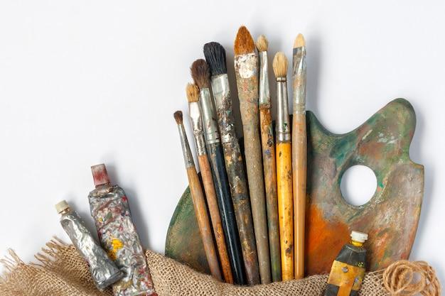 Escovas, paleta e tubos com tinta