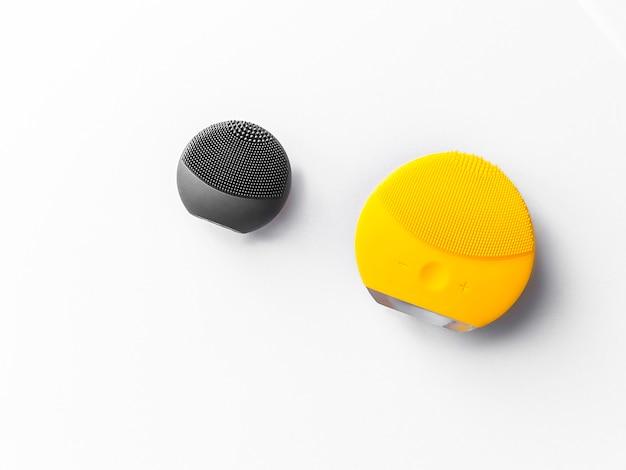Escovas pretas e amarelas do silicone para a lavagem da cara e os termas da cara isolados no fundo branco.