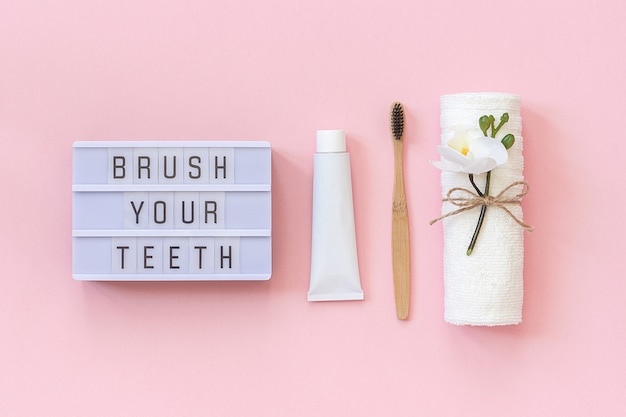 Escove os dentes - texto caixa de luz e escova de bambu natural eco-friendly para dentes, toalha, tubo de creme dental.