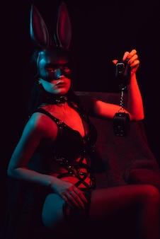 Escrava em lingerie sexy com máscara de coelho com algemas de couro
