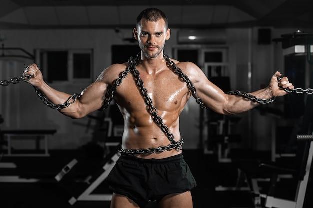 Escravo de homem musculoso em cadeias no ginásio, o prisioneiro
