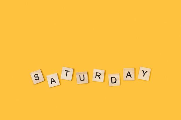 Escreve aos sábados com cubos de letras de madeira em um fundo amarelo