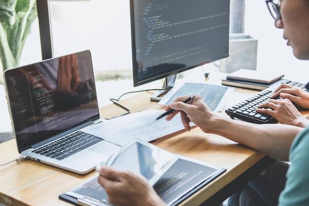 Escrevendo códigos e digitando tecnologia de código de dados, programador colaborando trabalhando em projeto de web site em desenvolvimento de software em computador desktop da empresa, programação com html, php e javascript.