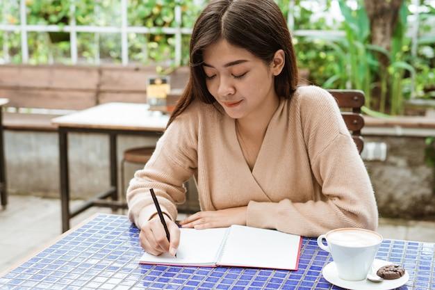 Escrevendo em seu caderno no café