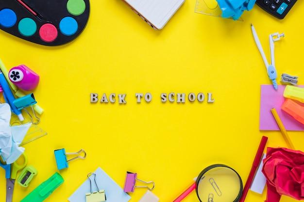 Escrevendo instrumentos colocados em círculo com as costas para as palavras da escola