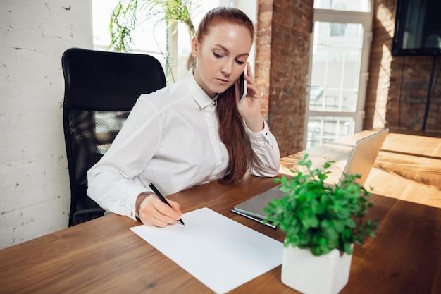 Escrevendo, ligando. mulher jovem caucasiana em traje de negócios, trabalhando no escritório. jovem empresária, gerente fazendo tarefas com smartphone, laptop, tablet tem conferência online. conceito de finanças, trabalho.