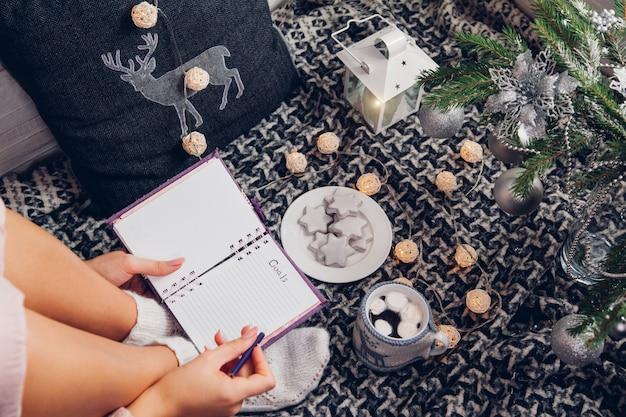 Escrevendo metas para o próximo ano com uma xícara de chocolate e biscoitos sob a árvore de natal