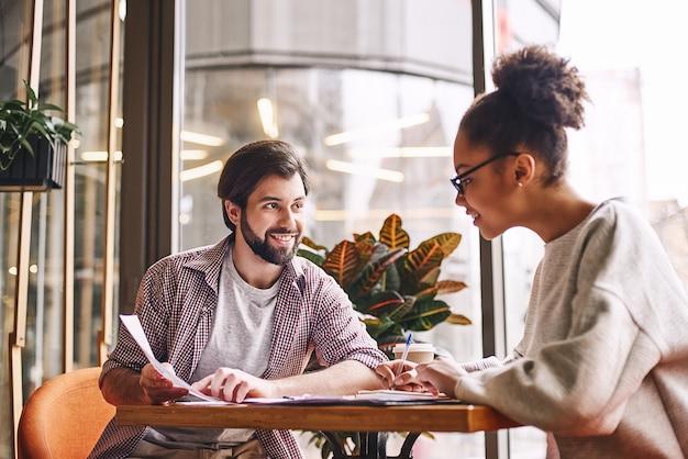 Escrevendo novas ideias, empresário barbudo apontando para o gráfico com um sorriso e discutindo algo