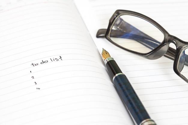 Escrevendo para fazer a lista na página do caderno com caneta em fundo de madeira