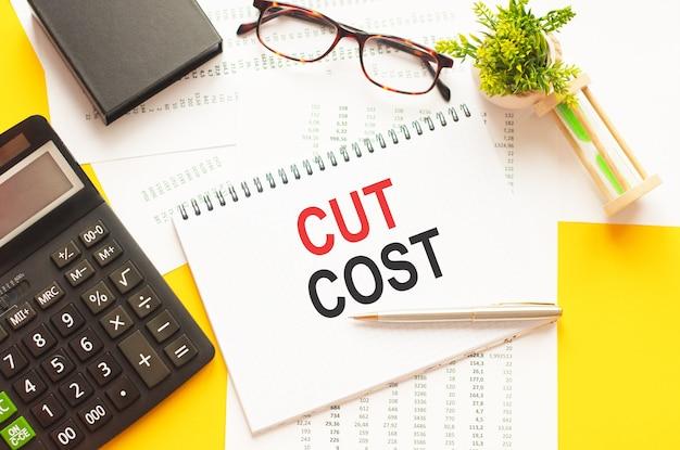 Escrevendo texto mostrando cut cost. escrever texto cut cost em cartão de papel branco, letras vermelhas e pretas, parede amarela. conceito de negócios.