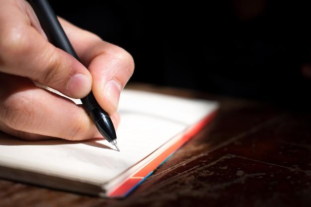 Escrevendo um livro sobre uma mesa de madeira. perto da janela com uma luz vermelha.