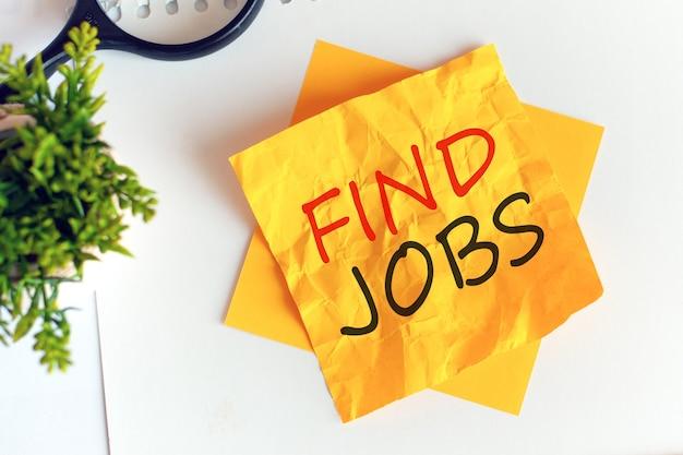 Escrever, encontrar empregos em papel amarelo amassado, local de trabalho, brainstorming. desfocar. letras vermelhas.