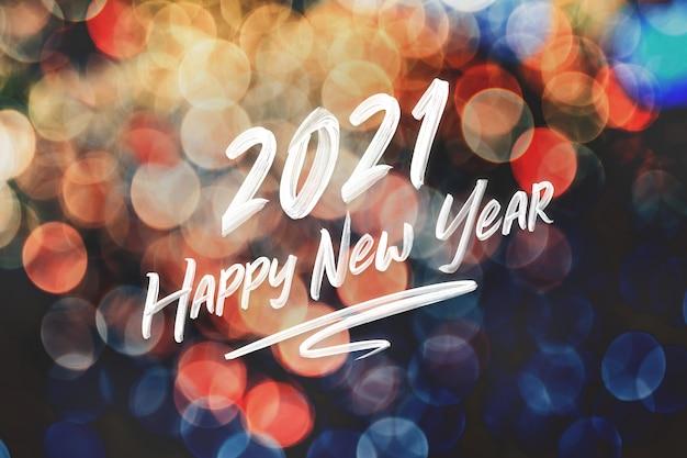Escrita à mão de pincelada de feliz ano novo de 2021 na luz do bokeh colorido festivo abstrato