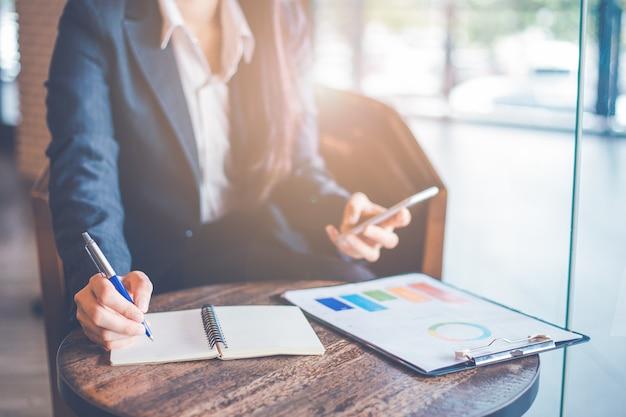 Escrita da mão da mulher de negócio em um bloco de notas com uma pena e utilização do smartphone no escritório.