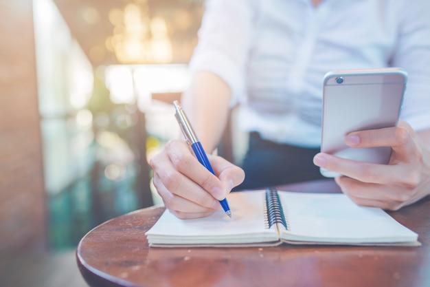 Escrita da mão da mulher em um bloco de notas com uma pena e utilização de um telefone celular no escritório.