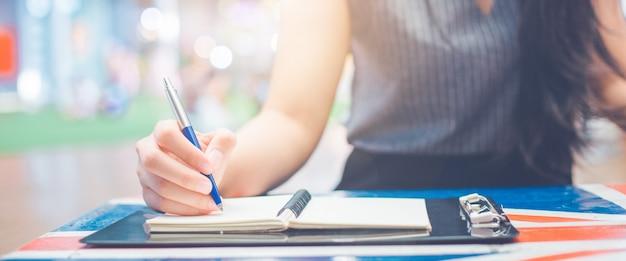 Escrita da mão da mulher em um bloco de notas com uma pena.