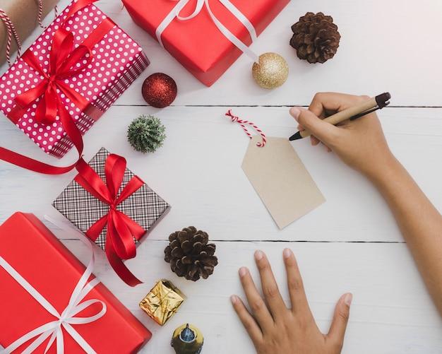 Escrita de mão na etiqueta de papel com caixa de presente de natal e ano novo com ornamento decorativo na mesa de madeira branca