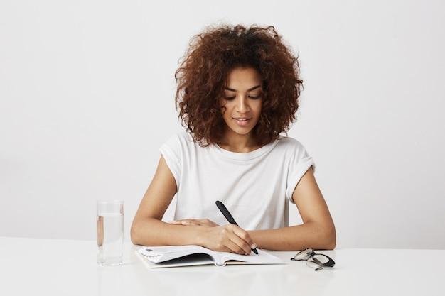 Escrita de pensamento da menina africana no caderno que sorri sobre a parede branca. copie o espaço.