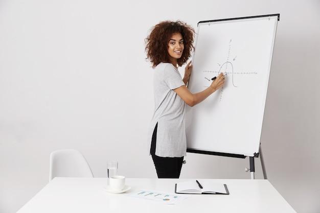 Escrita de sorriso da mulher de negócio africana no quadro branco do marcador.