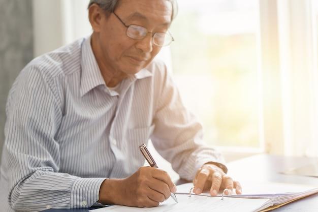 Escrita de trabalho superior asiática da mão ou contrato de seguro do sinal para o conceito futuro.