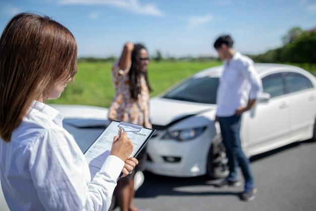 Escrita do agente de seguros na prancheta após carros do acidente.
