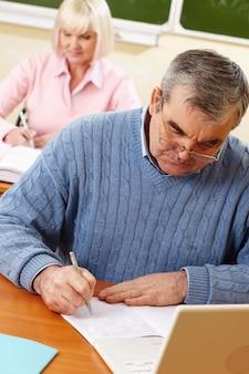 Escrita homem sério em seu notebook