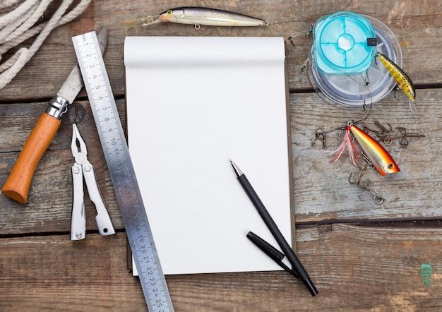Escrita-livro com equipamentos de pesca e ferramentas de design na placa de madeira
