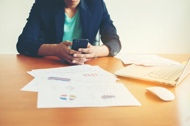 Escrita trabalhador em um telefone com o laptop e documentos