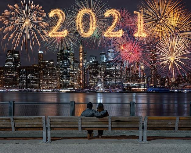 Escrito com sparkle fireworks com multicolor de fogos de artifício nas costas casal sentado e olhando para o fundo da paisagem urbana de nova york