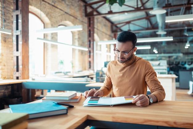 Escritor à mesa. escritor barbudo e bonito sentado à mesa escolhendo a cor da capa do livro