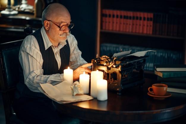 Escritor adulto trabalha em máquina de escrever vintage com luz de velas no escritório em casa. velho de óculos escreve romance de literatura em uma sala com fumaça, inspiração