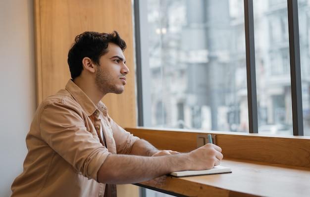 Escritor asiático pensativo, anotando, olhando pela janela