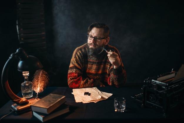 Escritor barbudo de óculos fumando cachimbo