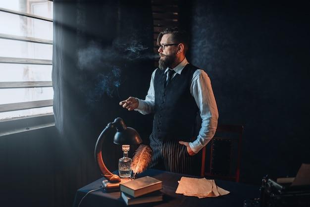 Escritor barbudo de óculos fumando um cigarro