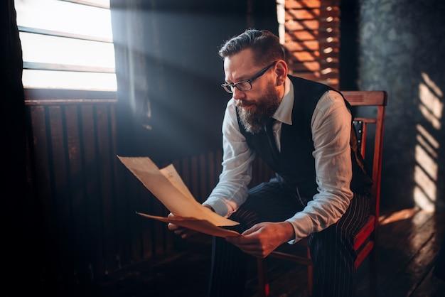 Escritor barbudo de óculos lendo texto manuscrito