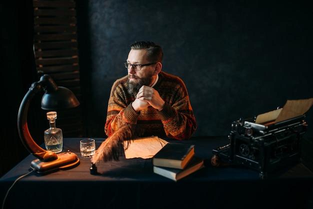 Escritor barbudo de óculos sentado à mesa