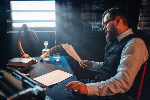 Escritor barbudo fuma e lê texto manuscrito