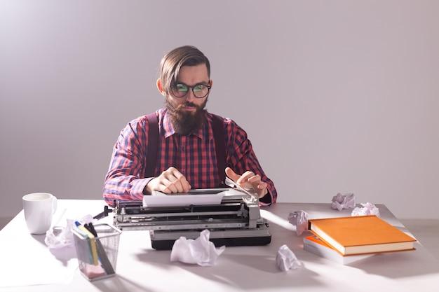 Escritor cercado de pedaços de papel focado no trabalho