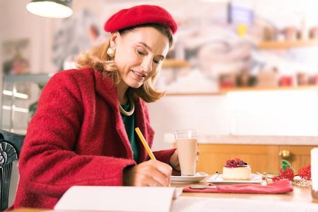Escritor com lápis. escritor francês de boina e casaco vermelhos segurando um lápis enquanto faz algumas anotações